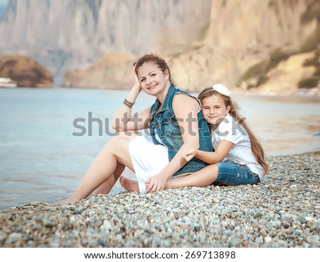 young beautiful woman with a child on the beach