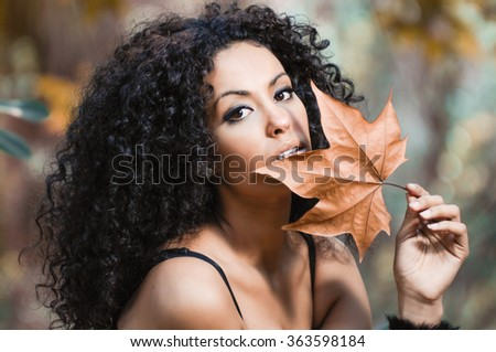 Young beautiful woman with a dry leaf in an urban park - stock photo