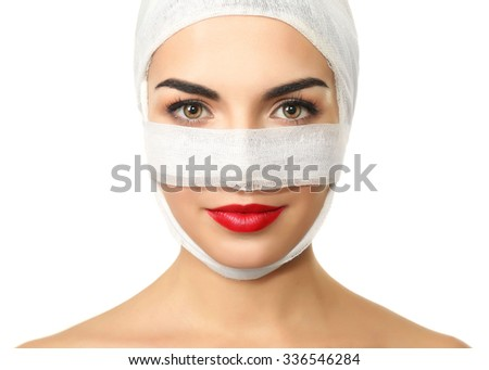 Young beautiful woman with a gauze bandage on her head and nose, isolated on white, close-up - stock photo
