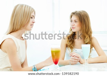 Young beautiful woman with a glass of drink sitting in a cafe