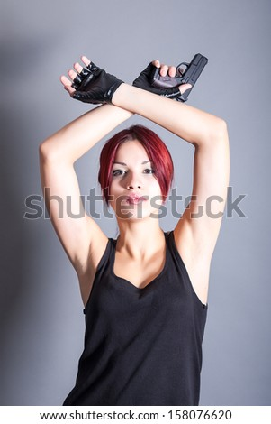 young beautiful woman with a gun - stock photo