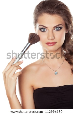 Young beautiful woman with a make-up brush, isolated on white - stock photo