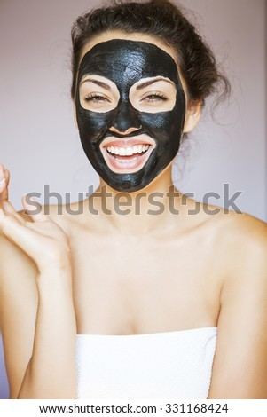 Young beautiful woman with a mask for the face of the therapeutic black mud - stock photo