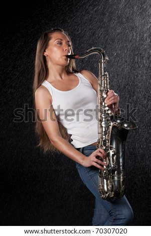 Young beautiful woman with a saxophone stands under rain on a black background. - stock photo