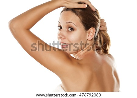 young beautiful woman with a towel on her chest posing on a white background