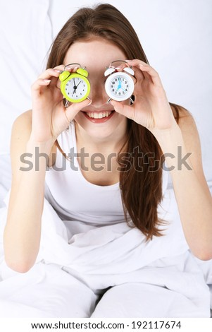 Young beautiful woman with alarm clocks in bedroom - stock photo