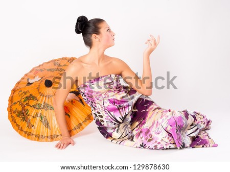 Young beautiful woman with asian umbrella at white background - stock photo