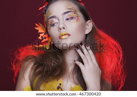 Young beautiful woman with autumn make up and leaves on head