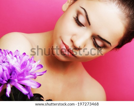 young beautiful woman with big purple flower over pink background - stock photo