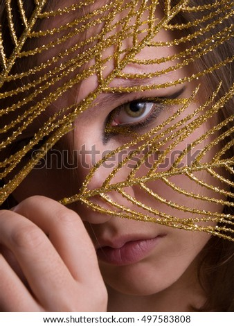 Young beautiful woman with black and gold eyeliner make-up looking through holded in hand golden feather. Close up.