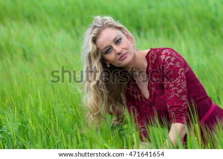 young beautiful woman with blond hair in a green grassy farmland field