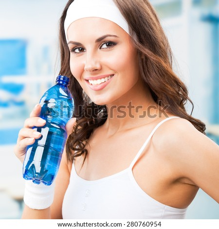 Young beautiful woman with bottle of water, at fitness club or gym - stock photo