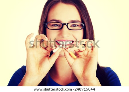 Young beautiful woman with broken cigarette. Stop smoking concept. - stock photo