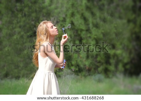 Young beautiful woman with bubbles outdoors
