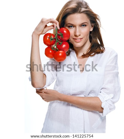 Young beautiful woman with bunch of tomatoes in hand / intriguing girl of european appearance in a white shirt holding a bunch of tomatoes - on a white background  - stock photo