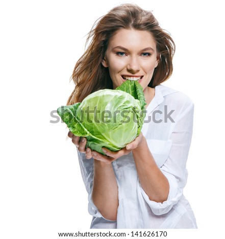 Young beautiful woman with 	cabbage head in hand / good-natured girl of european appearance in a white shirt holding a head of cabbage - isolated on white background  - stock photo