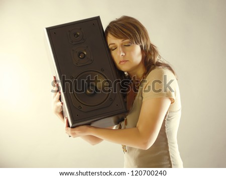 Young beautiful woman with closed eyes holding big wooden speaker and listening music - stock photo