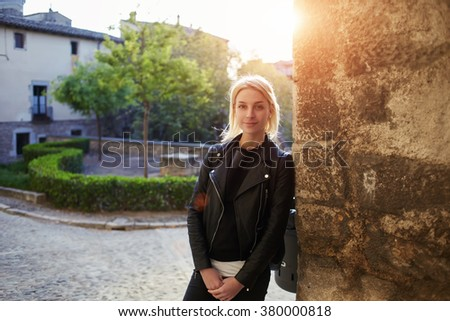 Young beautiful woman with cool style looking at camera while standing on the street in small beautiful city, pretty hipster girl posing while resting after walking outdoors during her spring weekend - stock photo