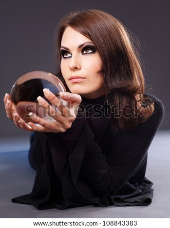 Young beautiful woman with crystal ball.