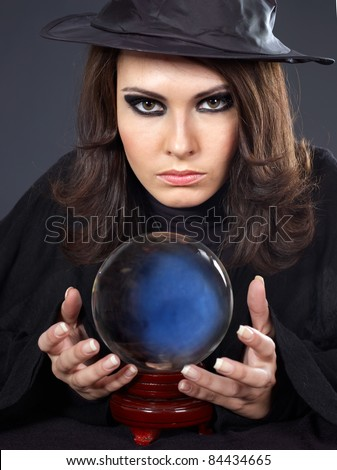 Young  beautiful woman with crystal ball. Fortune telling.