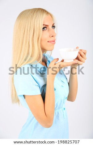 Young beautiful woman with cup of tea isolated on white