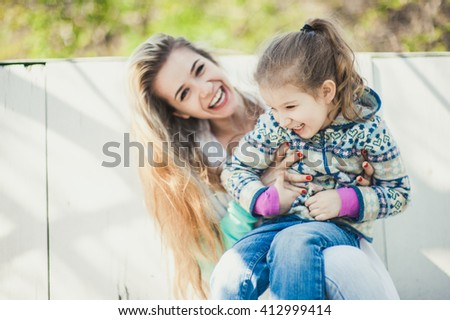 Young beautiful woman with cute child laugh and smile sitting on the white wood bench  - stock photo