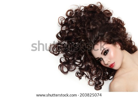Young beautiful woman with dark long curly hair over white background - stock photo