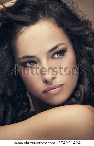 young beautiful woman with dark shiny wavy hair beauty portrait, studio shot, closeup - stock photo