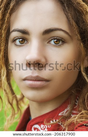 Young beautiful woman with dreadlocks in red clothes closeup. - stock photo