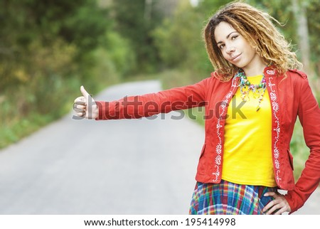 Young beautiful woman with dreadlocks in red clothes votes hitchhiking on road. - stock photo