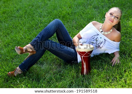 Young beautiful woman with drum on the green grass - stock photo