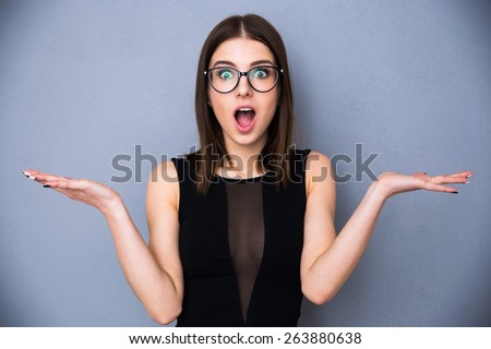 Young beautiful woman with facial expression of surprise standing over gray background. Wearing in trendy black dress and glasses. Looking at the camera - stock photo
