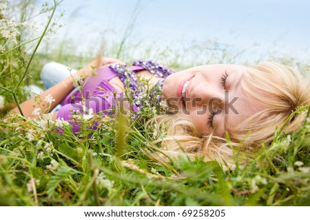 young beautiful woman with fair hair lying and  enjoy on the meadow - stock photo