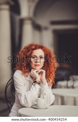 young beautiful woman with fiery red curly hair, sitting in a vintage retro cafe restaurant and coffee morning drink tasty cappuccino, nice table, outdoor portrait, close up, italy venecia - stock photo
