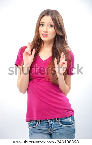 Young beautiful woman with fingers crossed on studio background. Concept of wishing or praying about something - stock photo
