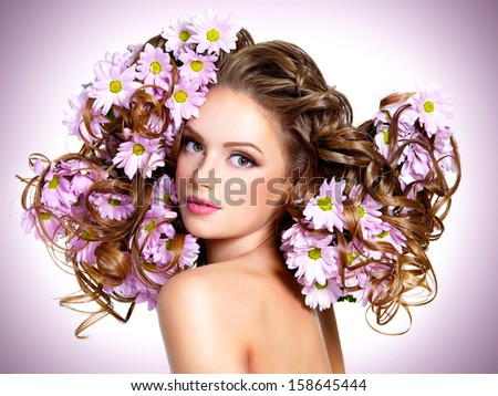 Young beautiful woman with flowers in hairs posing at studio
