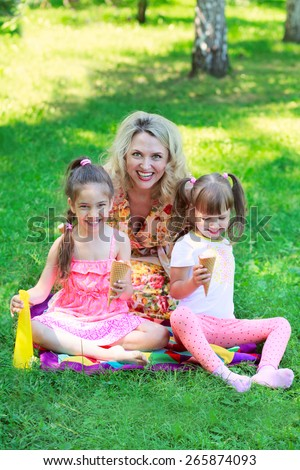 Young beautiful woman with girls kids daughters sitting on grass, smiling eating ice cream