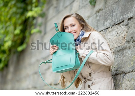Young beautiful woman with handbag. Funny young woman in the street - stock photo