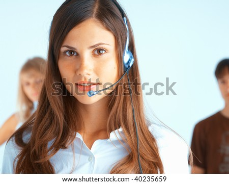 Young beautiful woman with headset with some people at the background - stock photo