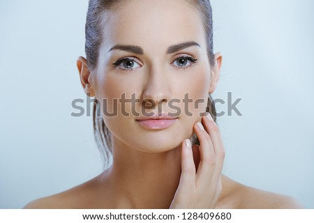 Young beautiful woman with health skin touching her neck - stock photo