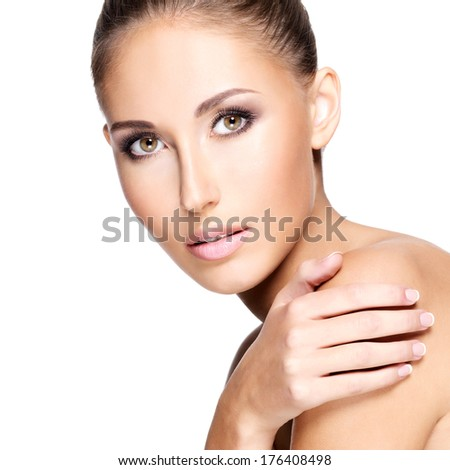 Young beautiful woman with healthy skin touching her shoulder,  isolated on white. - stock photo