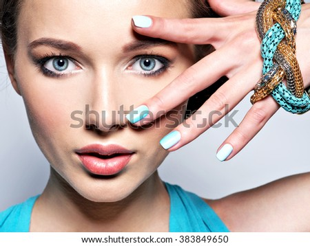 Young beautiful woman with jewelry.  Attractive model with blue nails.