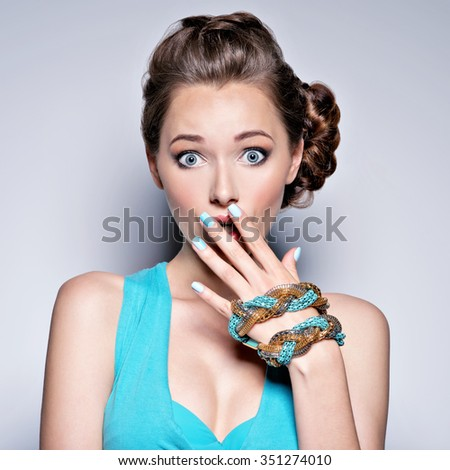 Young beautiful woman with jewelry. Girl Fashion  in blue dress . Attractive model with blue nails.  - stock photo