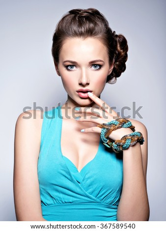 Young beautiful woman with jewelry. Girl Fashion  in blue dress. Attractive model with blue nails.  - stock photo