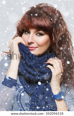 Young beautiful woman with knitted blue wool scarf wrapped around her neck. Snow flakes on the background.