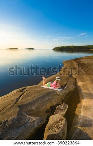 Young beautiful woman with laptop by the lakeside