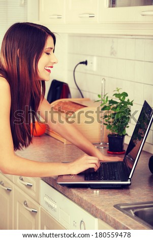 Young beautiful woman with laptop in the kitchen, looking for recipe  - stock photo