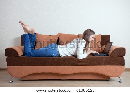 Young beautiful woman with laptop on the sofa - stock photo