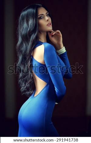 Young beautiful woman with long black curly hair posing in blue evening dress. Gorgeous stunning girl standing in dark interior. Fashion vogue style portrait - stock photo
