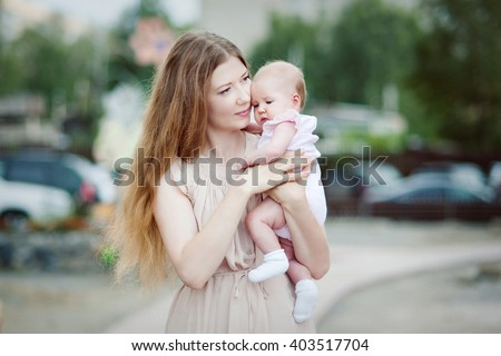 Young beautiful woman with long blond hair tenderly clutches his little daughter amid the urban landscape. - stock photo